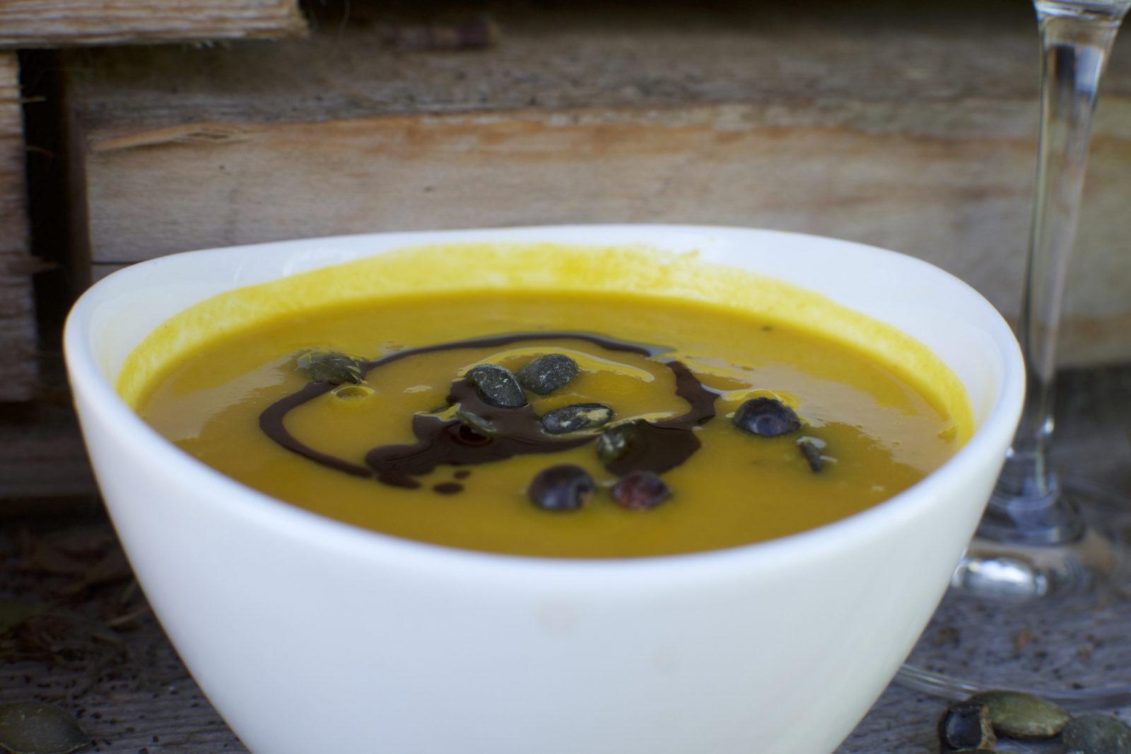 Kürbissuppe mit Kürbiskernöl angerichtet in weißer Schüssel vor einer Holzwand. Daneben steht ein Weinglas