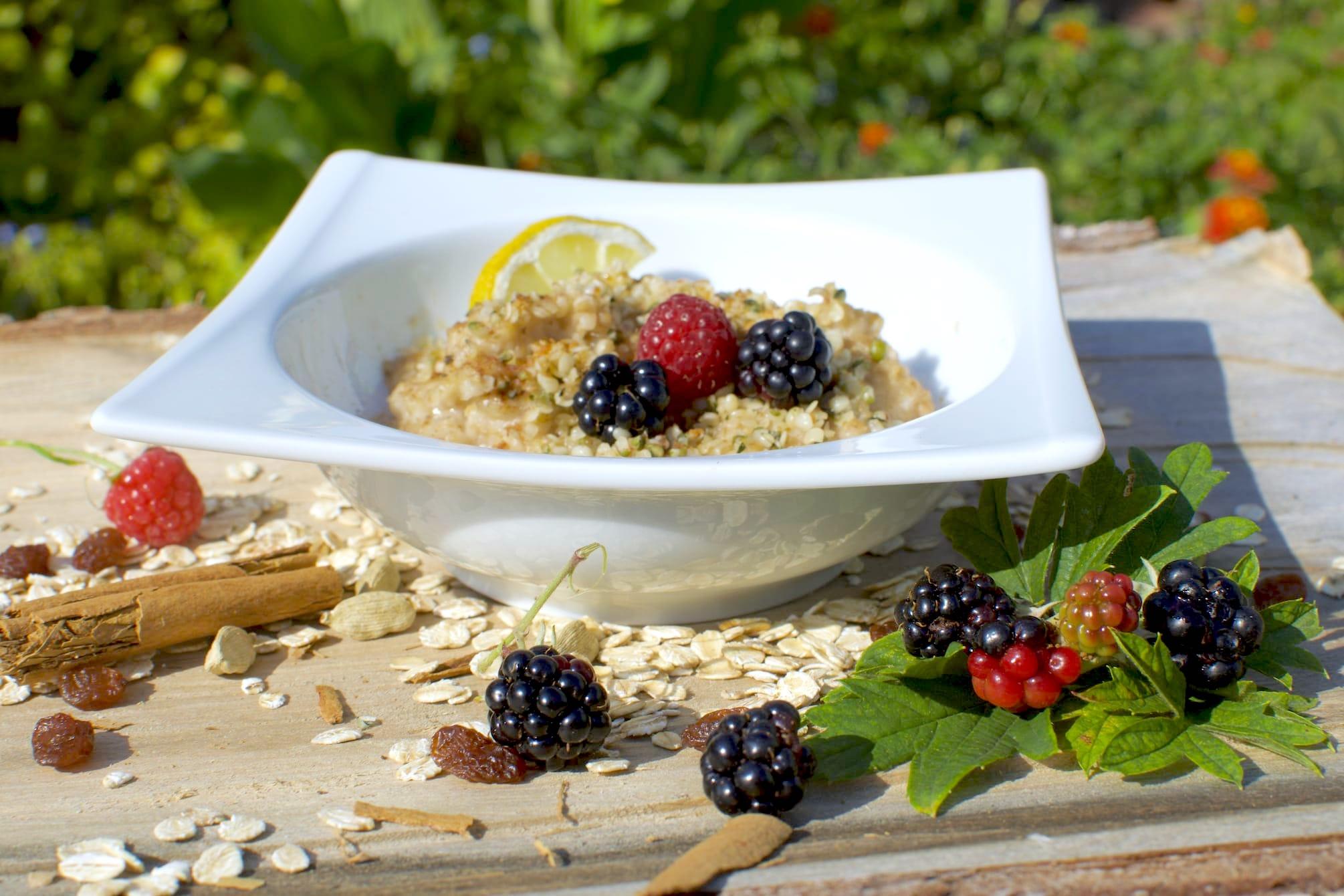 Porridge im Teller mit frischen Beeren und Dekoration auf einem Holzbrett