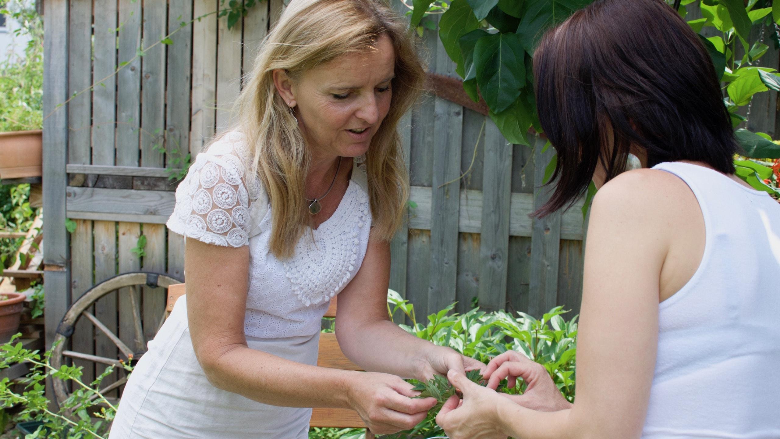 Gaby steht mit Kundin und erklärt ihr die Kräuter in ihrer Hand.