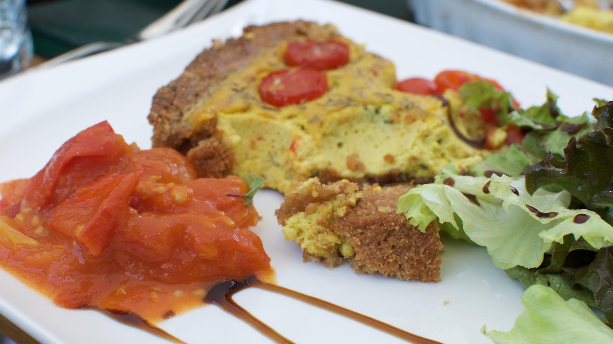 Ofentomaten, Quiche mit Salat drapiert auf einem weissen Teller