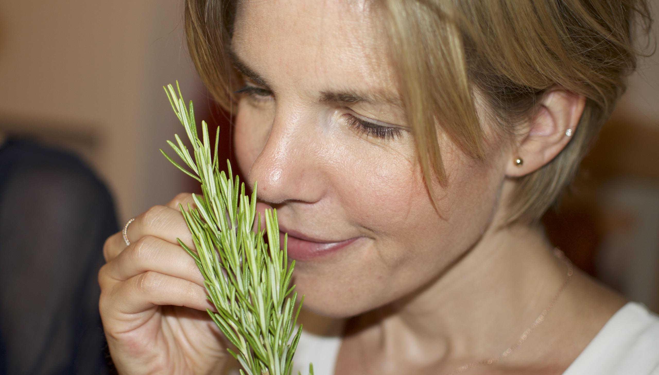 Frau mit blonden Haaren riecht an einem Rosmarinzweig. Porträtaufnahme